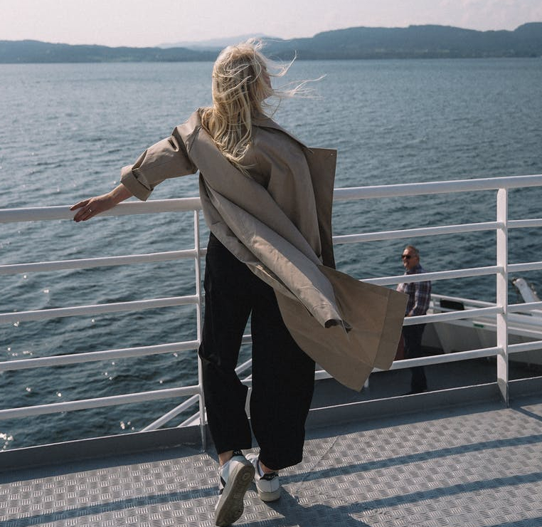 woman standing by the side of a watercraft